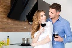 Pares felices que beben el vino rojo y que ligan en casa Imágenes de archivo libres de regalías