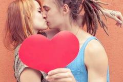 Pares felices que besan y que llevan a cabo el corazón en el fondo rojo de la pared Foto de archivo libre de regalías