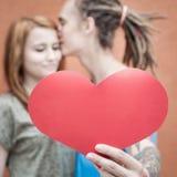Pares felices que besan y que llevan a cabo el corazón en el fondo rojo de la pared Fotos de archivo libres de regalías