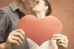 Pares felices que besan y que llevan a cabo el corazón en el fondo rojo de la pared Imagen de archivo