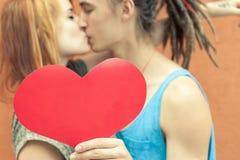 Pares felices que besan y que llevan a cabo el corazón en el fondo rojo de la pared Imágenes de archivo libres de regalías