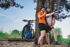 Pares felices que buscan en mapa en el destino del smartphone hombre y mujer en biking de montaña de los cascos que viaja sobre t fotos de archivo libres de regalías