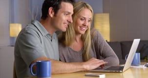 Pares felices que buscan una partida de las vacaciones en el ordenador portátil Imagen de archivo libre de regalías