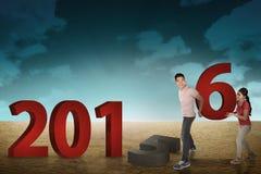 Pares felices que cambian el número 2015 con 2016 Imagen de archivo libre de regalías