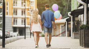 Pares felices que caminan abajo de la calle de la ciudad, sosteniendo los globos coloridos, fecha romántica Imagen de archivo