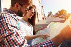 Pares felices que caminan al aire libre haciendo turismo y sosteniendo el mapa Imagen de archivo libre de regalías