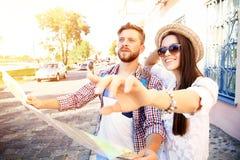 Pares felices que caminan al aire libre haciendo turismo y sosteniendo el mapa Fotografía de archivo libre de regalías