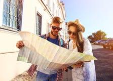 Pares felices que caminan al aire libre haciendo turismo y sosteniendo el mapa Imagen de archivo