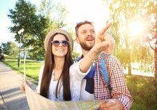 Pares felices que caminan al aire libre haciendo turismo y sosteniendo el mapa Foto de archivo