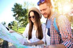 Pares felices que caminan al aire libre haciendo turismo y sosteniendo el mapa Fotografía de archivo