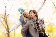 Pares felices que caminan en el bosque durante otoño imagenes de archivo