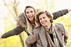 Pares felices que caminan en el bosque durante otoño imagen de archivo libre de regalías