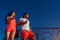 Pares felices que caminan en la ciudad en la puesta del sol Café de consumición del hombre joven y de la mujer y el caminar abajo Fotografía de archivo