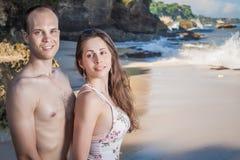 Pares felices que caminan en la playa, opinión del mar El viajar en Bali Imágenes de archivo libres de regalías