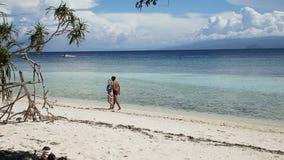 Pares felices que caminan en una playa tropical almacen de metraje de vídeo