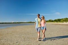Pares felices que caminan a lo largo de la playa del verano Imagenes de archivo