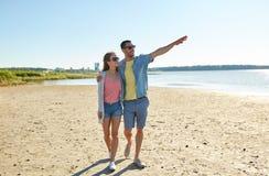 Pares felices que caminan a lo largo de la playa del verano Foto de archivo libre de regalías