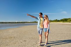 Pares felices que caminan a lo largo de la playa del verano Foto de archivo