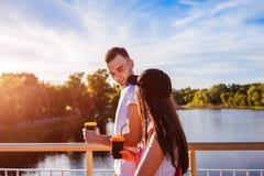 Pares felices que caminan a través del río en la puesta del sol Hombre joven y mujer que sostienen las tazas de café Fotos de archivo