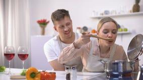 Pares felices que cocinan junto en la cocina, sopa que prueba femenina, comida sana almacen de metraje de vídeo