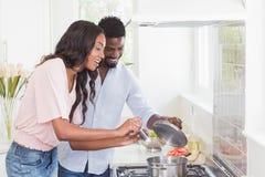 Pares felices que cocinan la comida junta Imagen de archivo