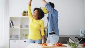 Pares felices que cocinan la comida y que bailan en casa metrajes
