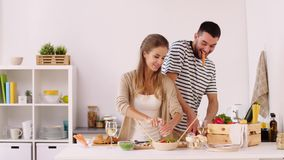 Pares felices que cocinan la comida y que se divierten en casa almacen de video
