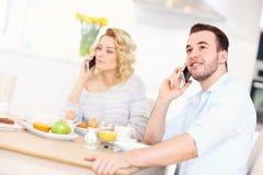 Pares felices que comen el desayuno y que usan el teléfono elegante foto de archivo