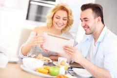 Pares felices que comen el desayuno y que usan la tableta foto de archivo
