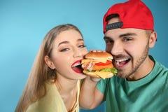 Pares felices que comen la hamburguesa foto de archivo libre de regalías