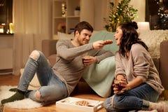 Pares felices que comen las galletas con cacao en casa Imagen de archivo