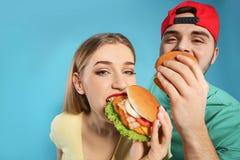 Pares felices que comen las hamburguesas imagen de archivo libre de regalías