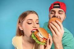 Pares felices que comen las hamburguesas imágenes de archivo libres de regalías