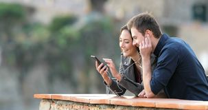 Pares felices que comparten música del teléfono elegante en un balcón