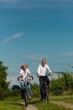 Pares felices que completan un ciclo al aire libre en verano Imagenes de archivo