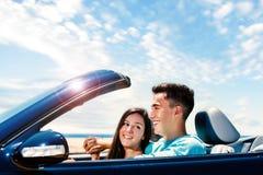 Pares felices que conducen el convertible a lo largo de la playa Imagen de archivo