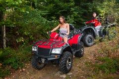 Pares felices que conducen los coches de cuatro ruedas ATV Foto de archivo libre de regalías