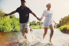 Pares felices que corren en agua poco profunda imagenes de archivo