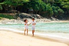 Pares felices que corren en la playa tropical Fotografía de archivo libre de regalías
