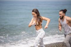Pares felices que corren junto al lado del agua en la playa foto de archivo libre de regalías