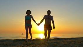 Pares felices que corren a lo largo de la playa que lleva a cabo las manos en el fondo de la puesta del sol metrajes