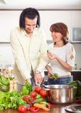Pares felices que cortan el apio para la ensalada en la cocina casera Foto de archivo