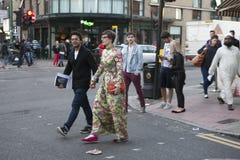 Pares felices que cruzan la calle en el área del carril del ladrillo Una muchacha en un vestido de largo florecido El hombre llev Fotografía de archivo libre de regalías