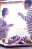 Pares felices que desayunan de anillos de espuma y del café en el mornin Imágenes de archivo libres de regalías