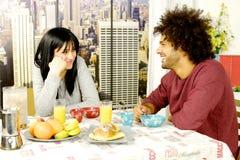 Pares felices que desayunan delante de rascacielos en ciudad Fotografía de archivo