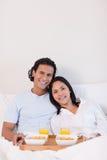 Pares felices que desayunan en la cama Imágenes de archivo libres de regalías