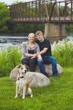 Pares felices que descansan por el puente con su perro Imágenes de archivo libres de regalías