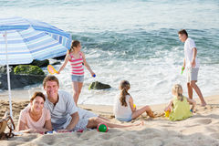 Pares felices que descansan sobre la playa con cuatro niños Imagen de archivo