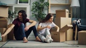 Pares felices que desempaquetan cosas después de la caja de la abertura de la relocalización que habla en piso metrajes
