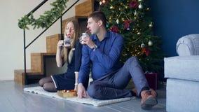 Pares felices que disfrutan de la bebida caliente debajo del árbol de navidad almacen de metraje de vídeo